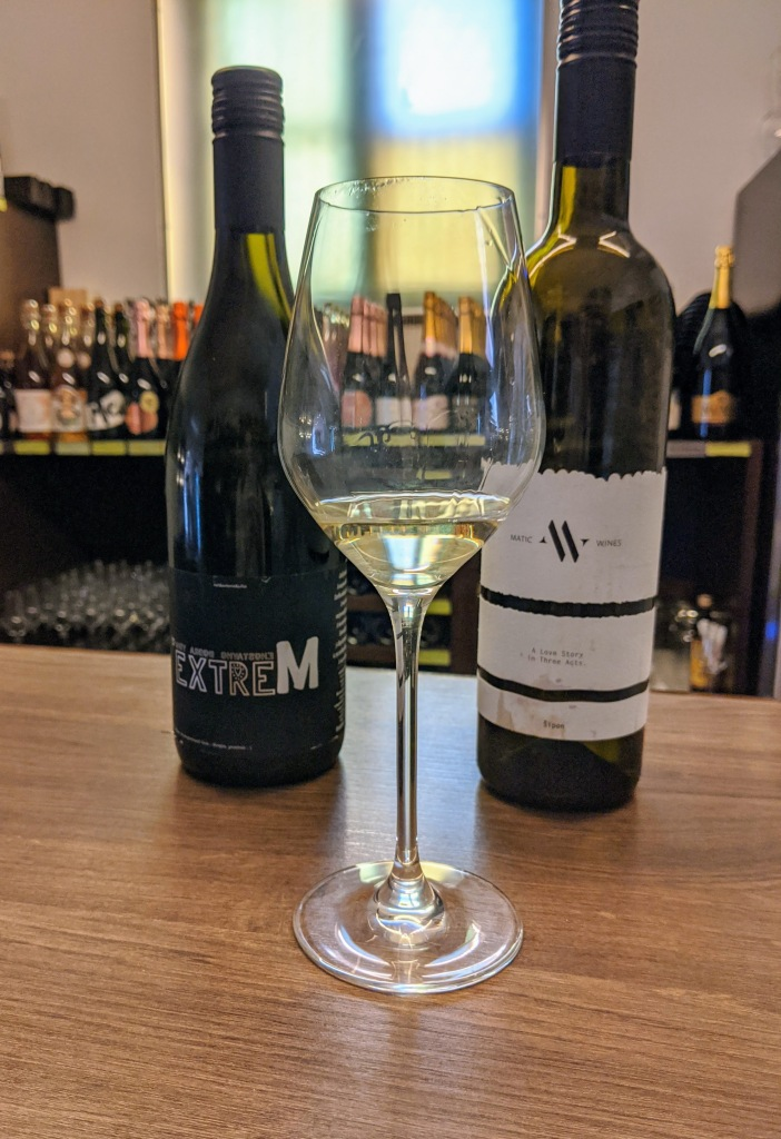close up of tasting glass of white wine in front of 2 bottles of wine in  a wine shop
